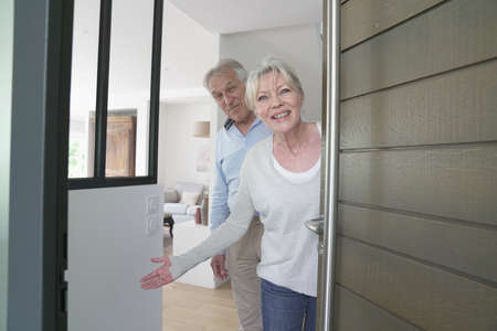 Senior people welcoming friends to enter home Фото со стока