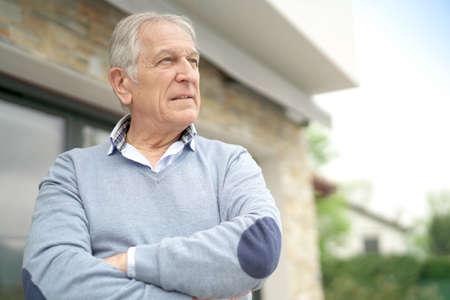 realestate: Senior man standing outside house