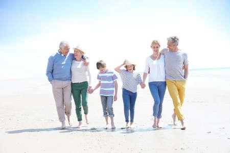 家族、両親、祖父母、孫、ビーチの上を歩く