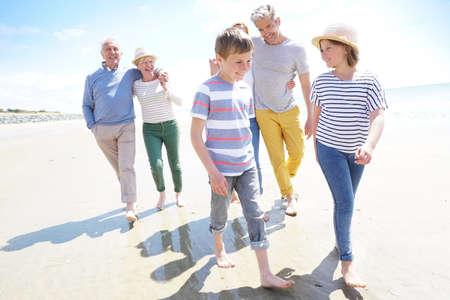 ビーチの上を歩く幸せな世代間の家族 写真素材