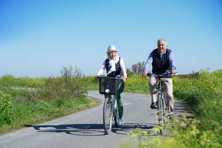 're: Senior couple riding bike together on country road