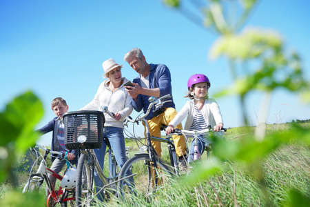 Family on a biking day making a stop and using smartphone Stock Photo