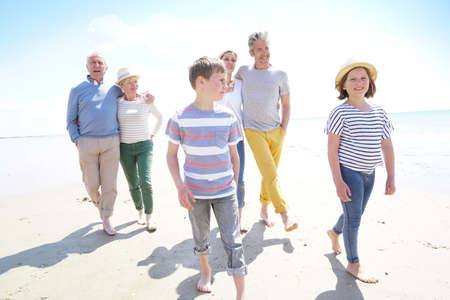 Happy intergenerational family walking on the beach
