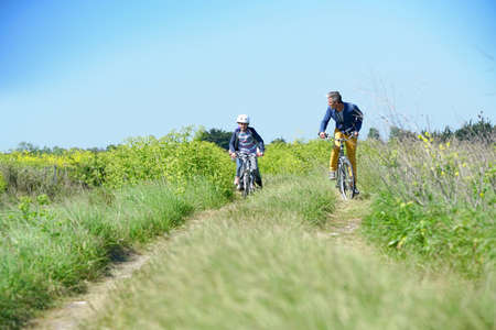 Father with kids riding bicycle in countyside Фото со стока