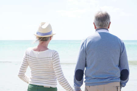 Back view of senior couple looking at the ocean Stock Photo