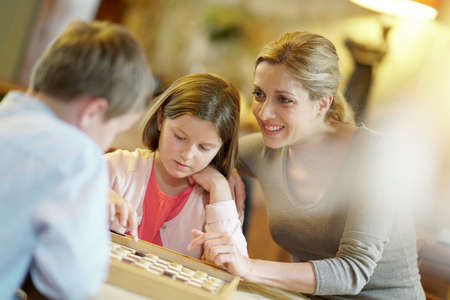 Mother with kids playing checkers at home