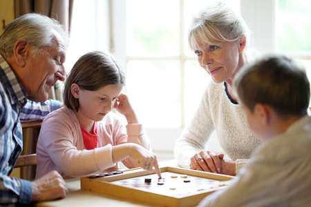 grandkids: Grand-parents with grandkids playing checkers