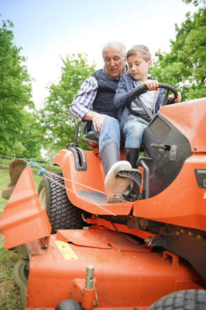 Senior man with grandkid riding on lawnmower