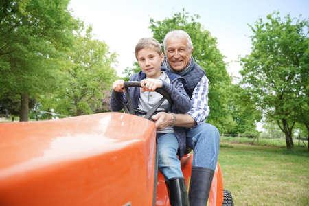 grandkid: Senior man with grandkid riding on lawnmower