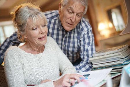 persona feliz: Senior pareja sentada en el escritorio mirando el álbum de fotos