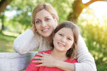 complicity: Portrait of mother and daughter sitting on bench outside