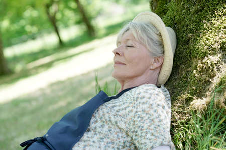 ツリーの庭でリラックスした年配の女性