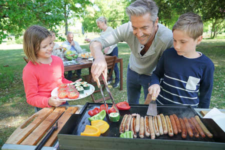 Father with kids preparing barbecue for family lunch 스톡 콘텐츠