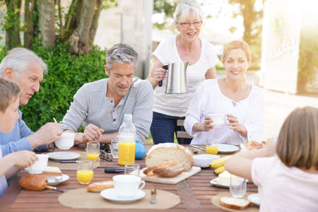 Family of 6 having breakfast together outside the house Stock Photo