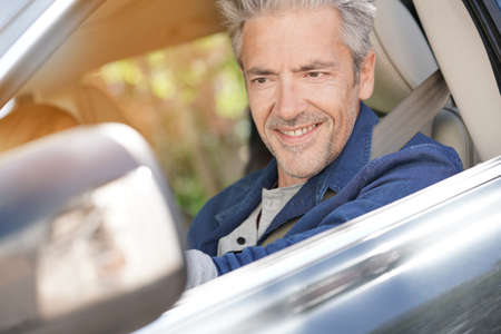 fastened: Portrait of mature man driving car