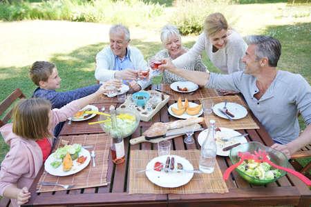 Family having summer lunch in garden