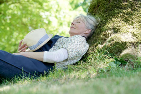 Senior woman relaxing in garden by tree Stock Photo
