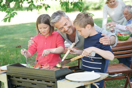 Father with kids preparing barbecue for family lunch Standard-Bild