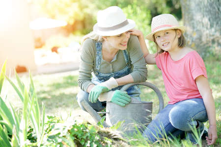 complicity: Portrait of mother and daughter gardening together