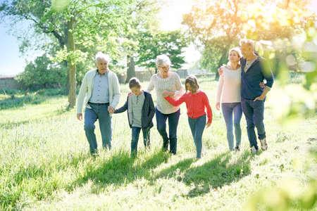 Happy family of 6 walking in park Stock Photo