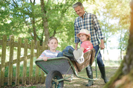 complicity: Daddy riding kids in wheelbarrow Stock Photo