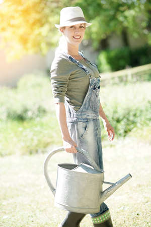 Young woman in garden holding watering can