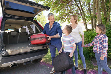 Happy family loading luggage in vehicle Stok Fotoğraf