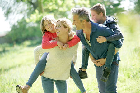 Parents giving piggyback ride to kids in countryside Stockfoto