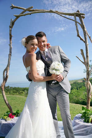 Bride and groom standing by an arch, ocean view Stock Photo