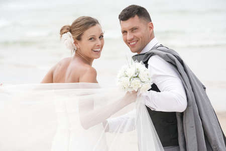 Cheerful just married couple walking on the beach