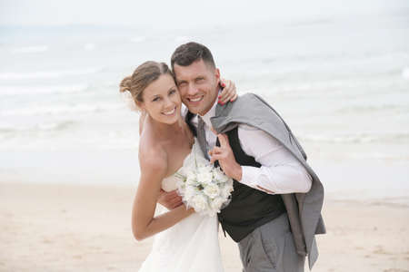 Portrait of happy bride and groom embracing each other at the beach