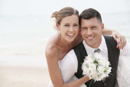 Groom giving piggyback ride to bride on the beach