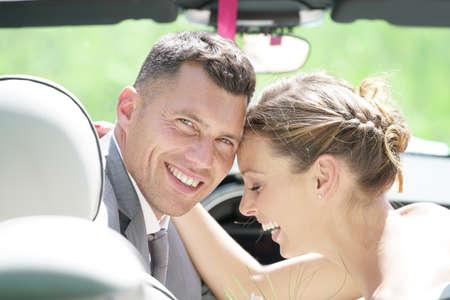 Bruid en bruidegom zitten in cabriolet Stockfoto
