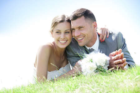Cheerful bride and groom relaxing in grass
