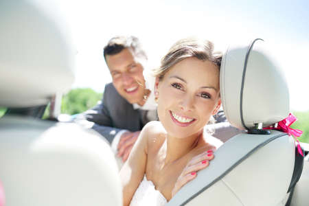 Portrait of beautiful smiling bride sitting in convertible car