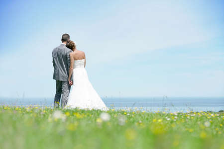 Bride and groom standing together in front of the sea
