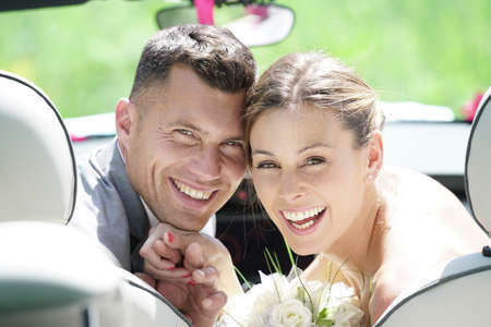 Bride and groom sitting in convertible car