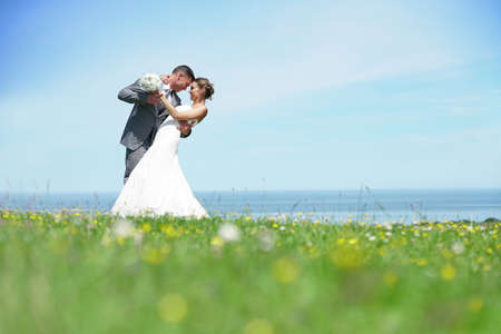 Groom embracing bride in front of the sea