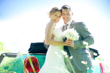 Bride and groom standing by convertible car on their wedding day Stock Photo