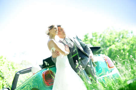 Beautiful couple on their wedding day standing by car Stock Photo