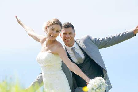 Bride and groom having fun walking in parapet Stock Photo