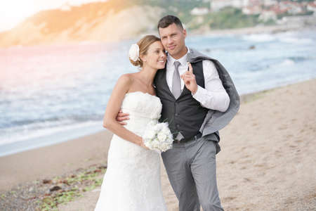 Happy bride and groom walking on beach at sunset Stock Photo