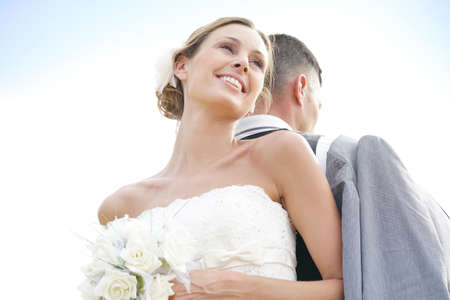 Cheerful bride standing back to back to groom Stock Photo