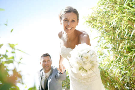 arm bouquet: Bride pulling on her grooms arm in countryside
