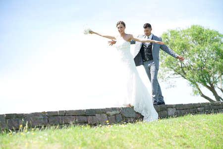 Bride and groom having fun walking on stone wall