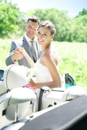 Groom leading bride to get in convertible car Stock Photo