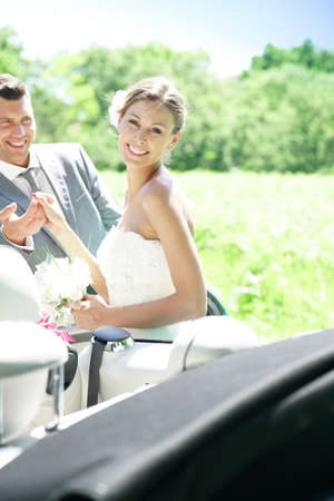 escorting: Groom leading bride to get in convertible car Stock Photo