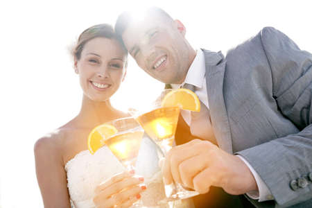 Bride and groom cheering with cocktails