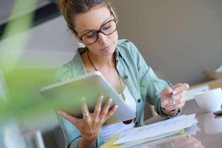 homeoffice: Trendy designer girl at home working on digital tablet