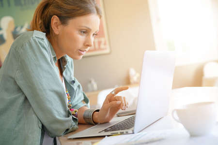 Young trendy woman at home working on laptop Stock Photo